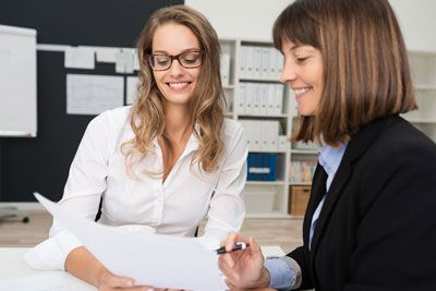 Close-up-Two-Happy-Young-Businesswomen-at-the-Office-Talking-About-Business-Report-on-Paper-new-compressor