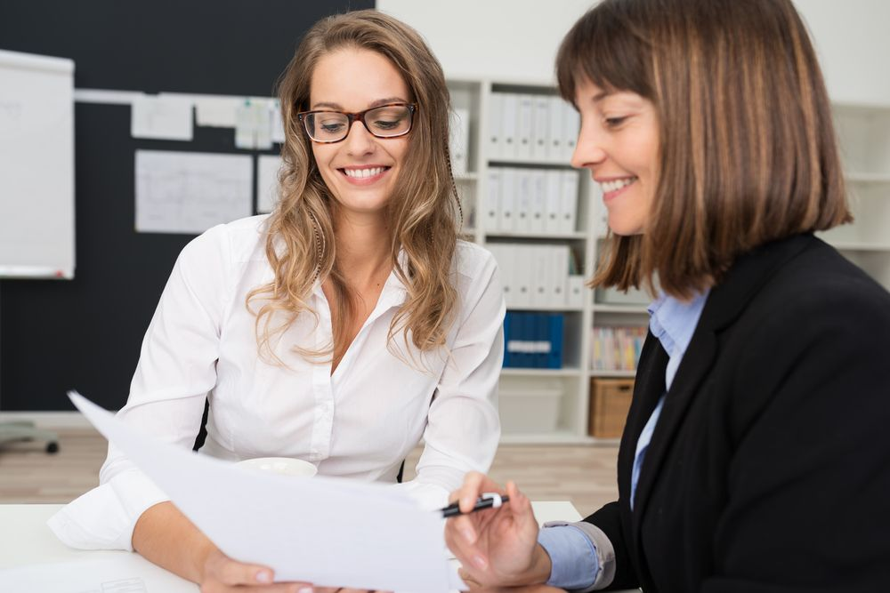 Close-up-Two-Happy-Young-Businesswomen-at-the-Office-Talking-About-Business-Report-on-Paper.-compressor